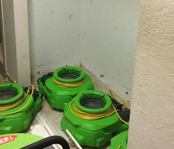 Green air movers drying a wall.