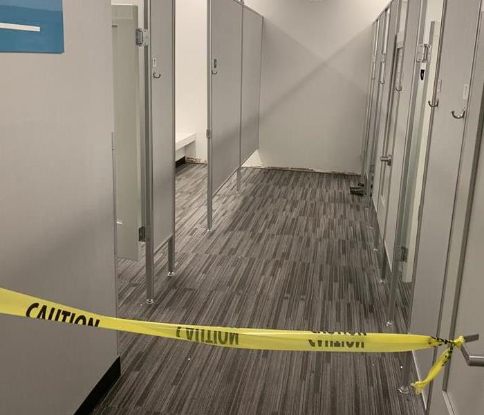 Hallway with grey carpet and yellow caution tape.
