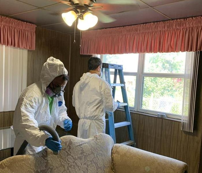 SERVPRO team members cleaning the floors in the room with pink and white curtains.