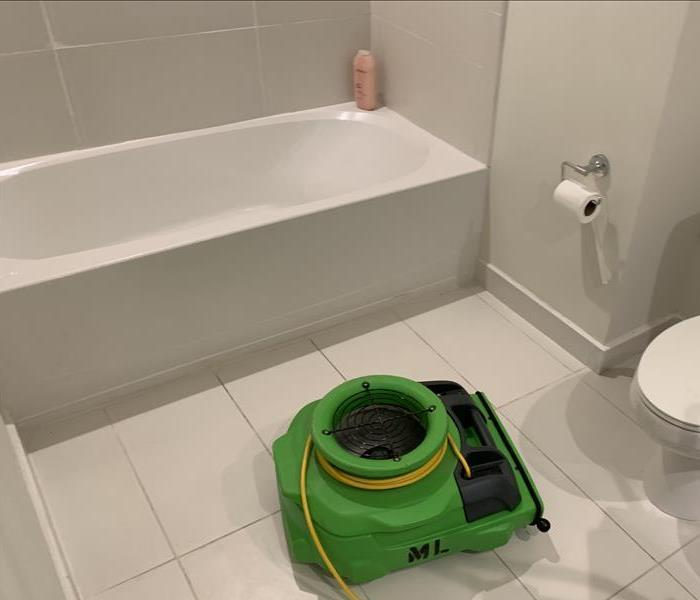 White bathtub shown with an air mover. The water loss was contained underneath the tile.
