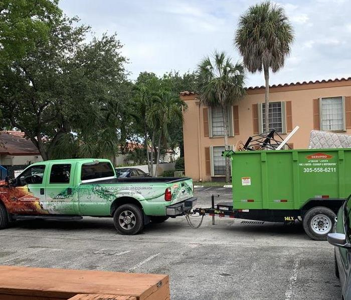 SERVPRO green truck toting around a dumpster full of moldy material.
