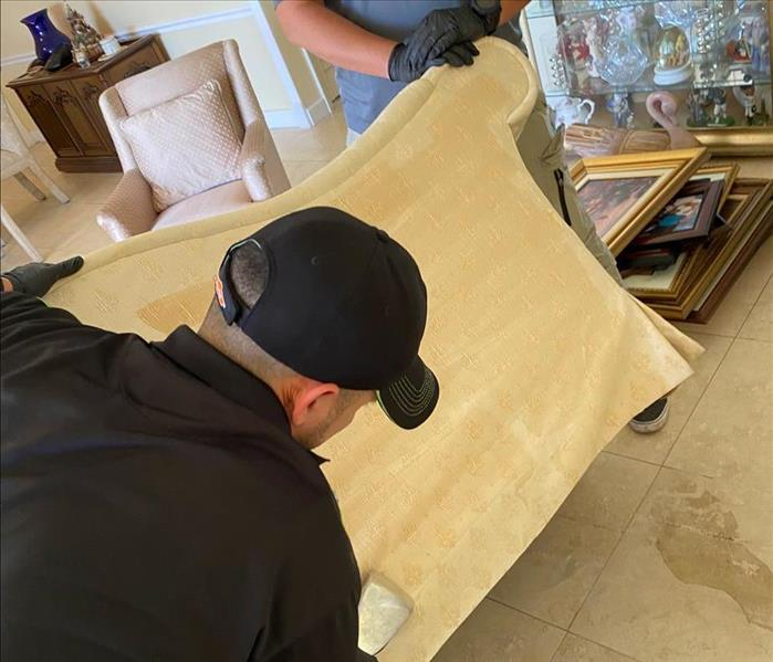 Two men cleaning a couch with a vacuum.