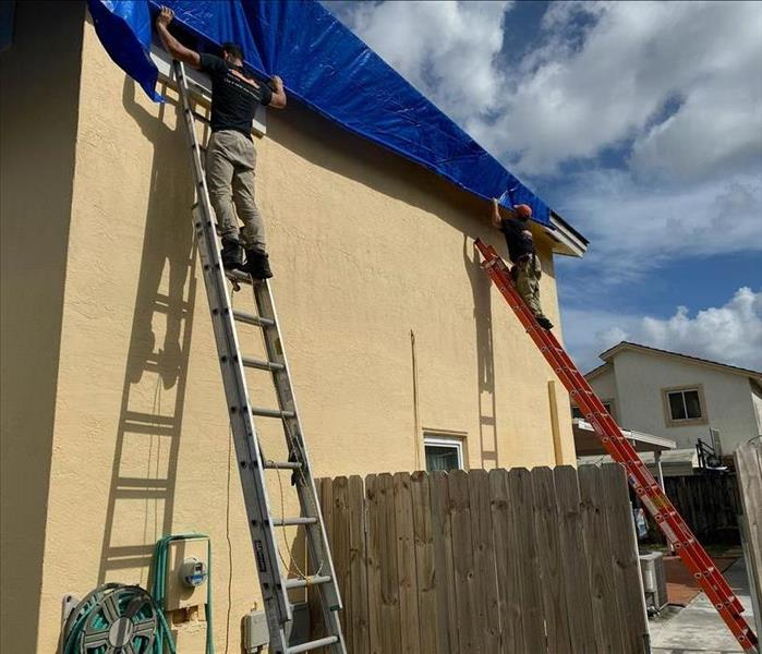 Two men on separate ladders holding on to a blue tarp.