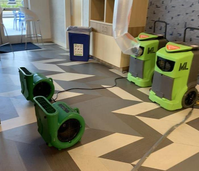 Grey and white flooring covered in green air movers and air scrubbers.