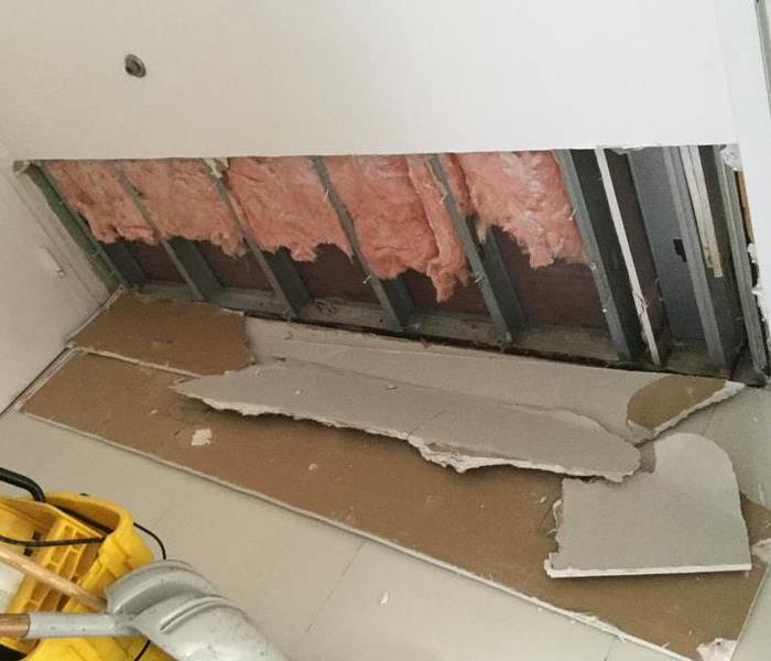 Drywall has been broken down and pink insulation is exposed.