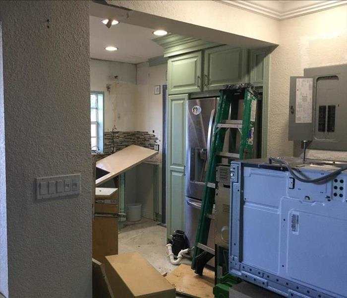 Kitchen with green cabinets and appliances pulled out.