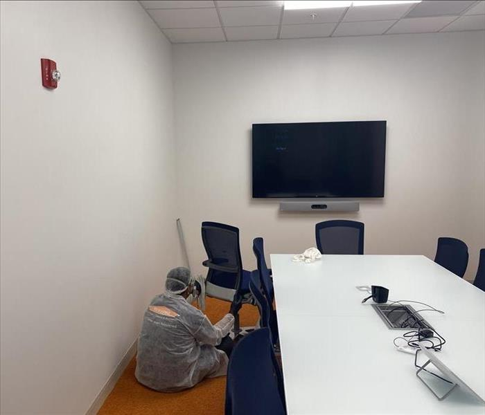 Conference room with employee sitting on the ground.