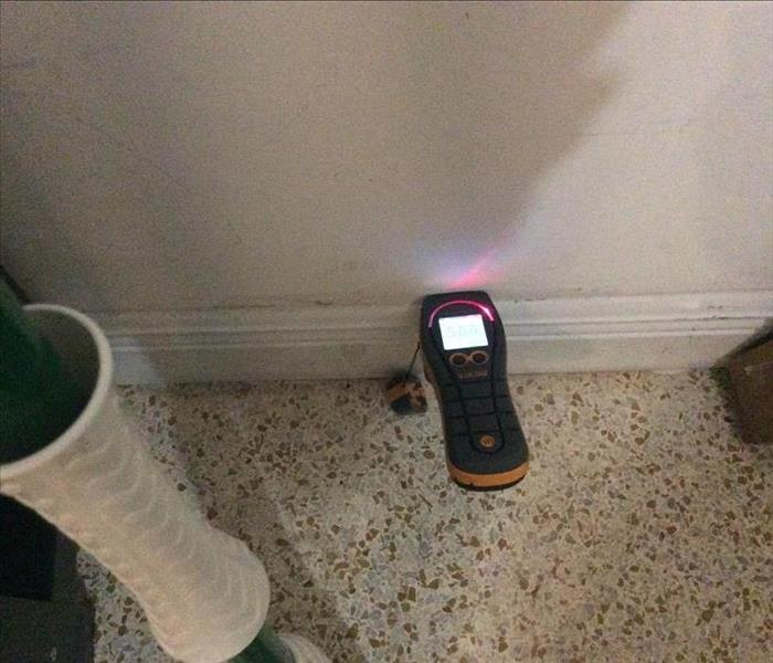 Moisture meter up against a white wall.