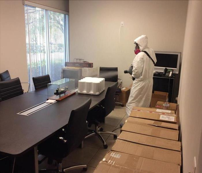Person in PPE using a HEPA air filter in an office.
