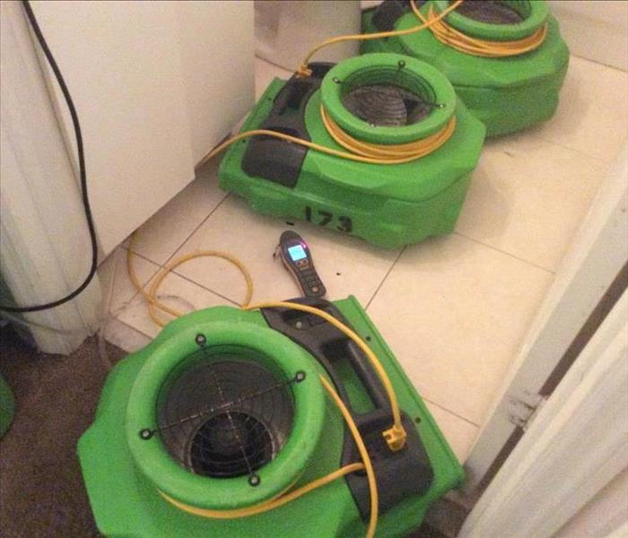 Three green air movers on a white tile floor.