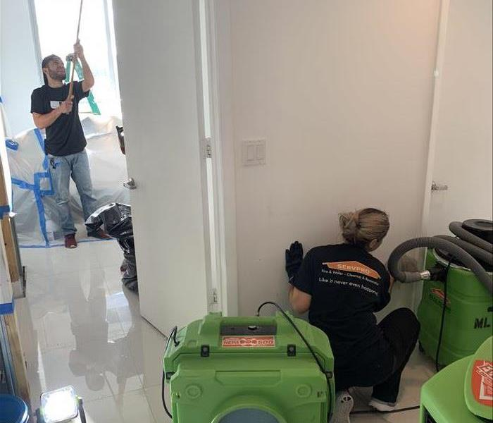 Employees cleaning and air movers drying the white floor.