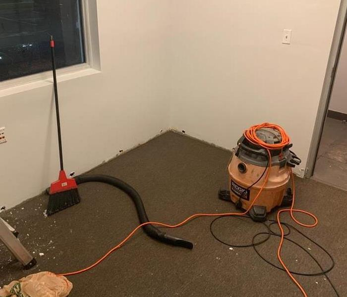 Water vacuum on the carpet flooring with orange cords.