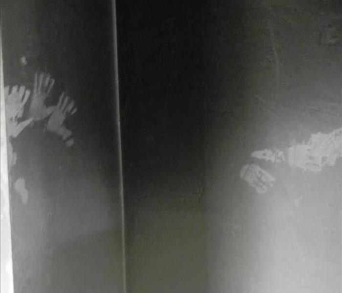 handprints on a wall with soot damage after a fire