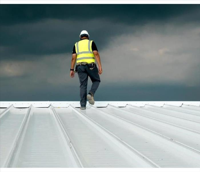 Construction engineer wearing safety uniform inspection metal roofing work for roof industrial concept