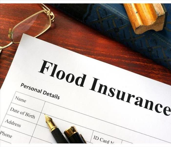 Flood insurance form on a table with a pen and glasses on a table